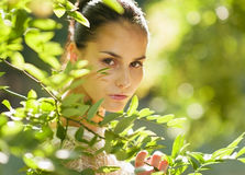 Portrait of girl hiding in foliage Stock Image