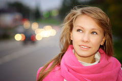 Portrait of girl about highway. Young beautiful woman against evening city street Stock Photography