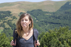 Portrait of girl hiker with backpack in the mountains surrounded Royalty Free Stock Images