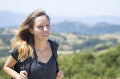 Portrait of girl hiker with backpack in the mountains surrounded Royalty Free Stock Photography