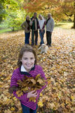 Portrait of girl holding autumn leaves with family in background Royalty Free Stock Photo
