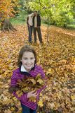 Portrait of girl holding autumn leaves with parents in background Stock Image