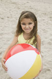 Portrait of girl holding beachball on beach smiling Stock Photos