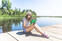 Portrait of girl holding book on wooden dock stock photos