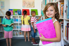 Portrait of girl holding books in school library Stock Photos