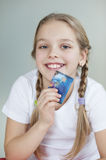 Portrait of a girl holding credit card over gray background Stock Photography
