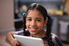 Portrait of girl holding digital tablet at home Stock Image