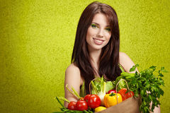 Portrait of a girl holding in hands full fruits Royalty Free Stock Photos