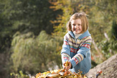Portrait of girl holding leaves near wheelbarrow Royalty Free Stock Images