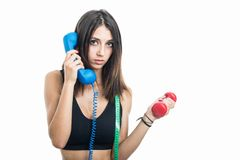Portrait of girl holding phone receiver and dumbbell Royalty Free Stock Image