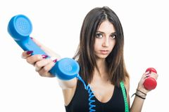 Portrait of girl holding phone receiver and dumbbell Royalty Free Stock Photo