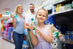 Portrait of girl holding plastic bottle with water in grocery sh. Portrait of smiling russian girl holding plastic bottle with water in grocery shop Stock Photos