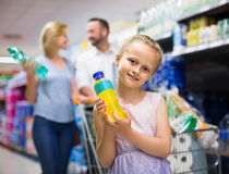 Portrait of girl holding plastic bottle with water in grocery sh Stock Photography