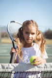 Portrait of girl holding racket and tennis ball. At court on sunny day Royalty Free Stock Images