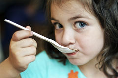 Portrait of  girl holding spoon in mouth Royalty Free Stock Photos