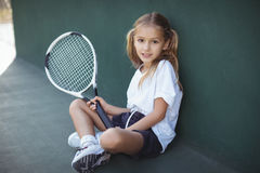 Portrait of girl holding tennis racket. While sitting at court Stock Photography