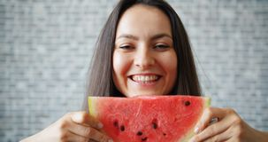 Portrait of girl holding water melon smiling hiding face on brick background. Portrait of pretty girl holding fresh water melon smiling hiding face standing on stock video footage