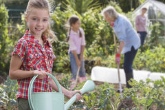 Portrait of girl holding watering can in garden Stock Photos