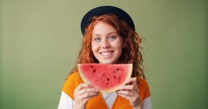 Portrait of girl holding watermelon smiling hiding face on green background. Portrait of joyful girl in trendy hat holding fresh juicy watermelon smiling hiding stock video footage