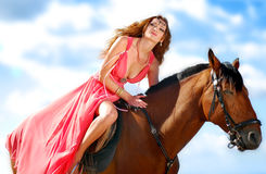 The portrait of a girl on a horse with a beach. And sky blue  background Royalty Free Stock Image
