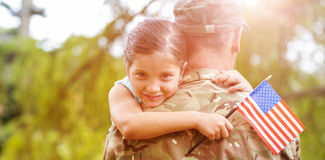 Portrait of girl hugging army officer father. Portrait of smiling girl holding american flag while hugging army officer father in park Stock Photos