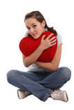 Portrait of a girl hugging a big red plush heart Stock Photography