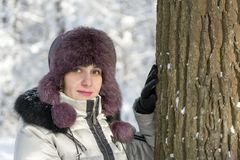 Portrait of a girl in a jacket and hat in a forest near a tree. Day, winter, royalty free stock photos