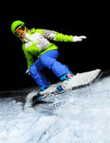 Portrait of girl jumping on snowboard at night Royalty Free Stock Image