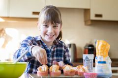 Portrait Of Girl In Kitchen Decorating Home Made Cupcakes Stock Photos