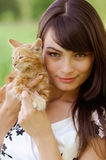 Portrait of girl with kitten. The young beautiful dark-haired woman holds in hands of a red kitten Royalty Free Stock Photo