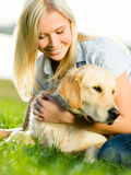 Portrait of girl with labrador on grass Stock Photography