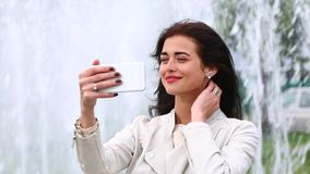 Portrait of girl laughing using smartphone. Pretty young woman with her mobile phone on fountain background. Pretty happy woman us stock footage