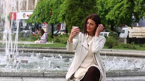 Portrait of girl laughing using smartphone. Pretty young woman with her mobile phone on fountain background. Pretty happy woman us. Portrait of girl laughing stock video footage