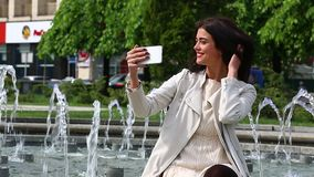 Portrait of girl laughing using smartphone. Pretty young woman with her mobile phone on fountain background. Pretty happy woman us. Portrait of girl laughing stock footage