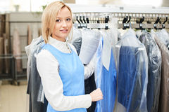 Portrait of a girl Laundry worker on the background of the coat racks Royalty Free Stock Photography