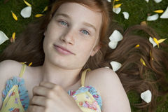 Portrait of Girl Laying on Grass and Petals Stock Images