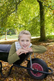 Portrait of girl laying in wheelbarrow Royalty Free Stock Image