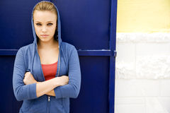 Portrait of a girl leaning against a blue painted wall stock image