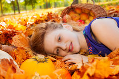 Portrait of girl on leaves with pumpkin and apples Stock Images