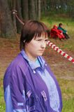 The portrait girl in a lilac sweater  in forest. The girl observes  competitions in wood Royalty Free Stock Photo