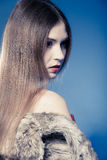 Portrait of girl with long hair. Young woman in fur coat on blue. Stock Images