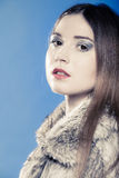 Portrait of girl with long hair. Young woman in fur coat on blue. Royalty Free Stock Photo