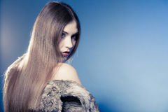 Portrait of girl with long hair. Young woman in fur coat on blue. Stock Photos