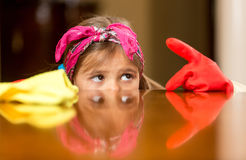 Portrait of girl looking at finger in gloves covered with dust Stock Images