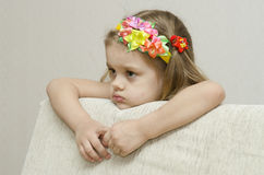 Portrait of a girl that looks thoughtfully left leaning his elbow on the back of the sofa royalty free stock photography