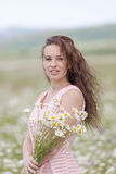 Portrait of girl with loose hair in chamomile field Stock Photos