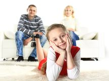 A portrait of a girl lying on the floor and smiling with her parents Stock Image