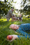 Portrait of girl (11-13) lying in grass with apple, parents and brother (9-11) in background Stock Photography