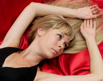 Portrait girl lying on a red background Royalty Free Stock Photography