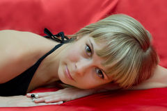 Portrait girl lying on a red background Stock Images
